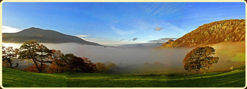 Mist at dawn over valley at Capel Curig with Snowdon behind